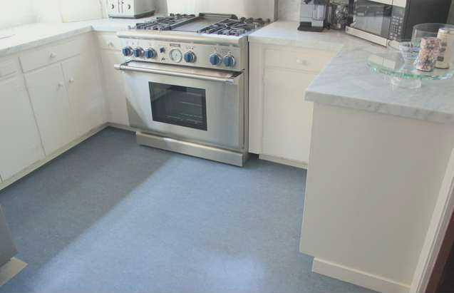 Open plan kitchen design with dark green cabinetry and marmoleum